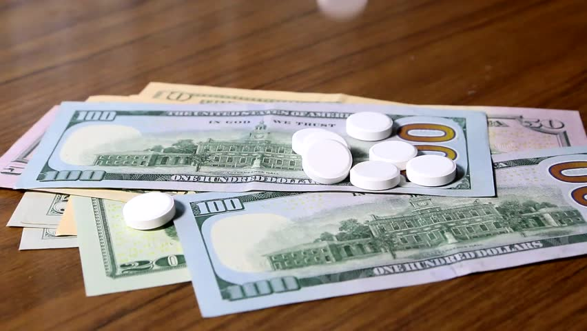 A small pile of American paper dollars and pill medications | Shutterstock HD Video #30256981
