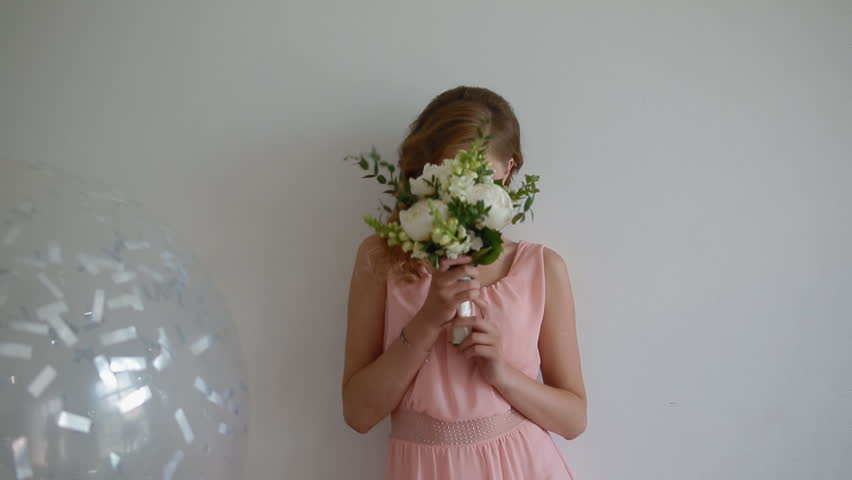 Portrait of caucasian bridesmaid with bouquet. Young woman holding flowers and smiling.