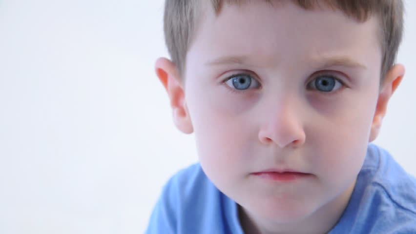 A young boy is wearing a blue t-shirt and looks seriously into the camera on a white background.
