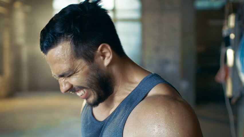 Exhausted Muscular Man Screams In Anger after Exhausting Gym Workout. He Wipes Sweat from His Face, He Wears Singlet. Shot on RED EPIC-W 8K Helium Cinema Camera.