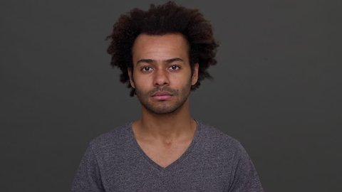 Dark-skinned man with afro haircut standing with apologetic glance and nodding negatively isolated over charcoal background