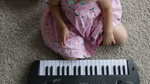 Child little girl playing on a toy piano. Full HD video