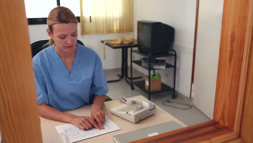 Nurse looking at files at a reception desk in a hospital