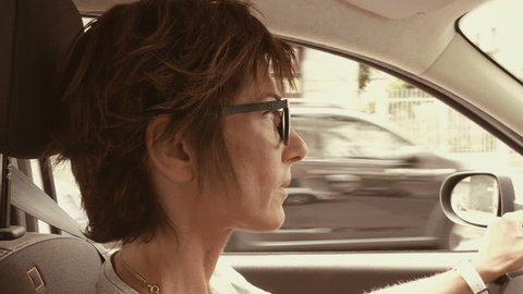 Woman with eyeglasses driving car with hands on steering wheel. Interior close up, side view, traffic on street. Vintage filter, toned image, slow motion.