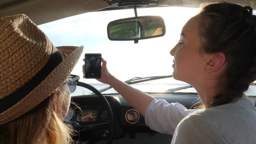 Selfi photo on smartphone of girlfriends behind wheel auto at Happy journey on coast sea, Summer | Shutterstock HD Video #30368491