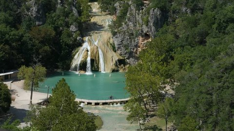 Steady wide aerial footage of Turner Falls on a bright sunny day  The 77-foot Turner Falls is one of the most popular summer destinations in Davis, Oklahoma