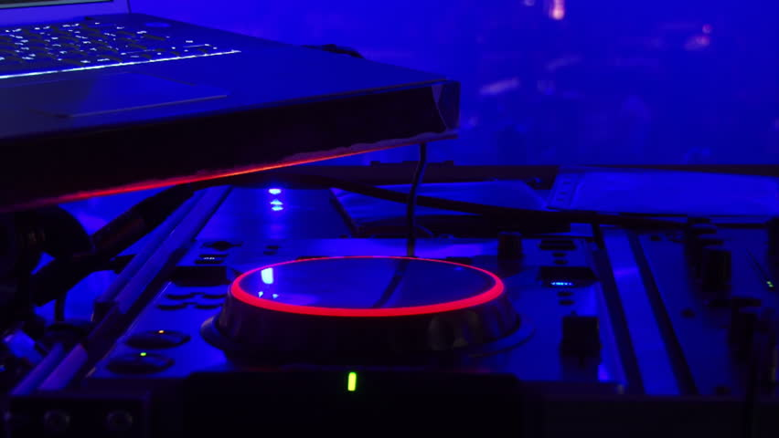 DJ equipment, people dancing background against blue light. Disc jockey. Blue lights.
