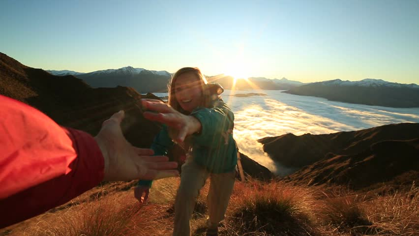 Teammate helping hiker to reach summit . Couple hiking in New Zealand, hand reach out to help female hiker reach the summit. A helping hand concept