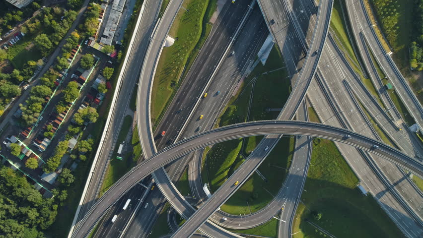 Multi-level road interchange and cars traffic. Drone is spinning around and flying up. Aerial vertical shot.