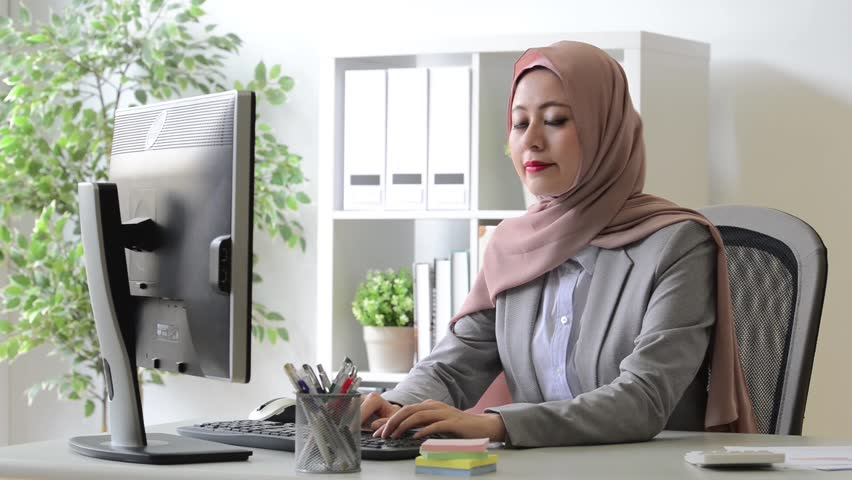 Pretty young muslim office employee woman using desk computer working and typing word and smile face to camera