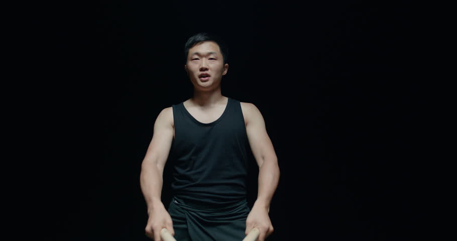 the beginning of a performance of Taiko , Asian male drummer in black clothes jumps with a scream and begins to beat the rhythm