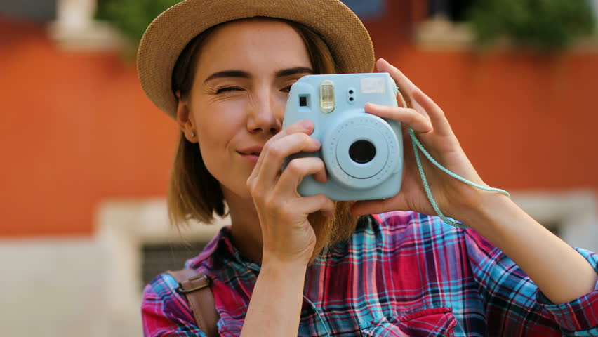 Close up shot of beatiful woman taking pictures on the stylish blue camera on the orange wall background.