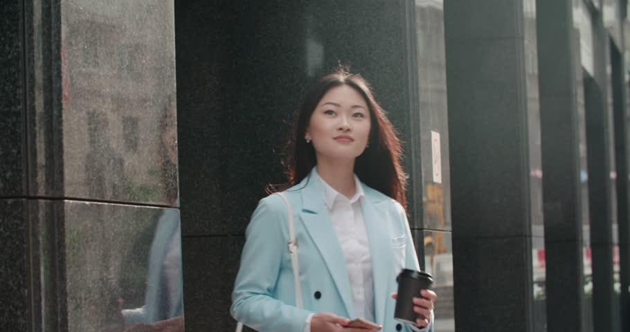beautiful young business Asian woman in a good mood in the morning, goes to work with smartphone and coffee to go, slow motion