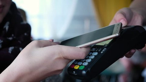 Contactless payment with your smartphone. Paying with a smartphone device on a credit card terminal. Wireless payment.