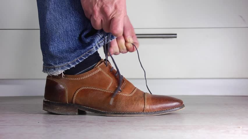 58b20da1d7299e Close up of a man wearing jeans tying the shoe laces of his brown leather  shoe