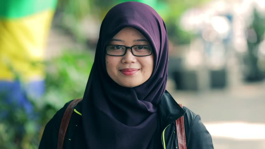 Portrait of beautiful south east asian muslim woman with hijab smiling on camera with three kind of tones (cyan - orange, contrast, and raw)