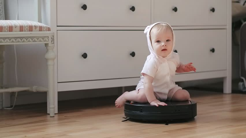 Funny baby girl sitting on spinning robot vacuum cleaner while cleaning room