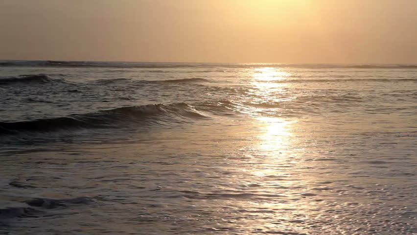 Surfer running into ocean and surfing while sunset