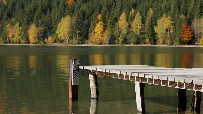 Wooden pontoon over a mountain lake mirroring the autumn colorful trees of the forest