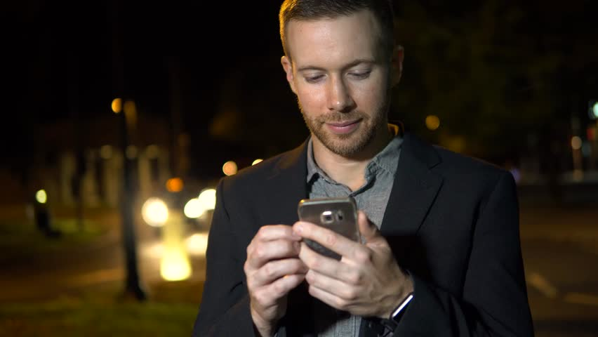 Man Using Mobile Phone at Night in City with Traffic, Texting or Browsing Online. | Shutterstock HD Video #30502474