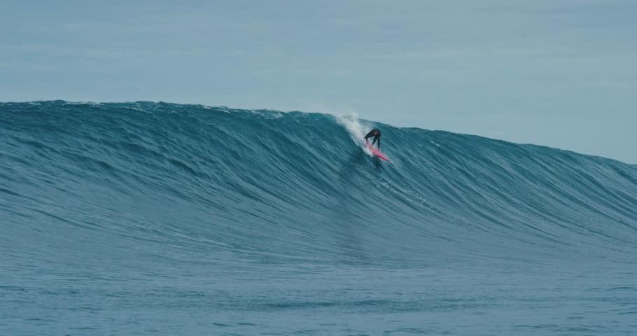 Surfer rides giant blue ocean wave. Shot on RED in 4k. Big wave surfing.