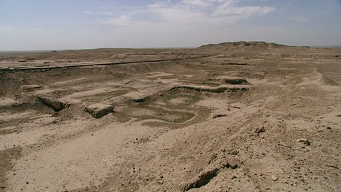 WARKA, IRAQ - CIRCA 2002: WIDE SHOT of ziggurat with Stone-Cone temple ruins in the foreground,, part of the Eanna district of Uruk. The Eanna district was dedicated to Sumerian goddess Inanna.