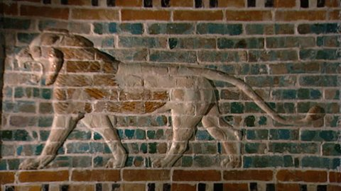HILLAH, IRAQ - CIRCA 2002: Replica from the Babylon site museum of the glazed brick relief of a striding lion from the palace of Nebuchadnezzar II. Original on display in the Royal Ontario Museum.