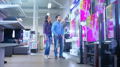 In the Electronics Store Professional Consultant Approaches Young Couple with His Expert Advice on Which of New Models of 4K TV's is Best for Their Home and Budget. Shot on RED EPIC-W 8K Helium Camera
