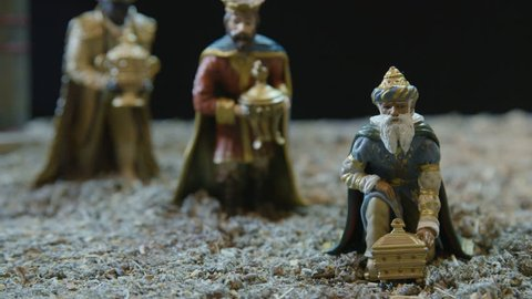 Closeup of the three kings with their gifts adoring the Child Jesus. Nativity scene figurines. Christmas traditions.