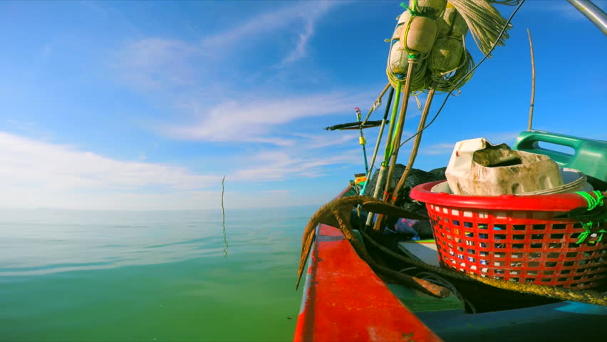 Wooden fishing boat in the sea with a big rusty anchor and some baskets aboard, view from the boats railing