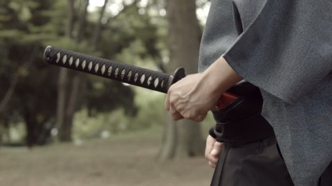 The Hands of Japanese Samurai drawing the sword called Katana.