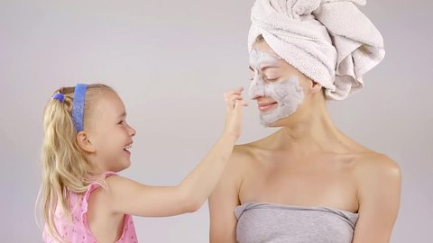 little girl with blonde hair is smiling and touching cosmetic mask on a face of her mother