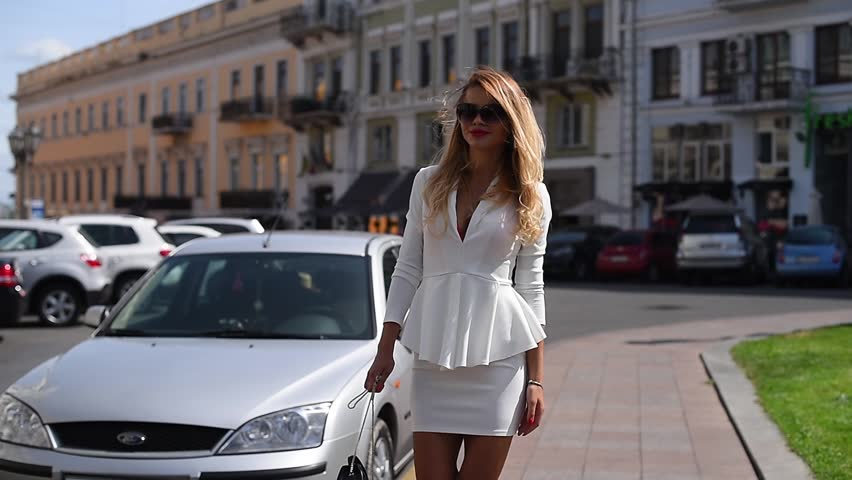 The girl is walking along the square past expensive cars in a white business suit. sunny warm day, blonde hair is fluttering in the wind. slender figure, graceful gait