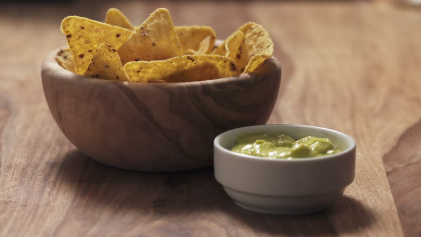Slow motion young female hand dipping nachos in guacamole sauce