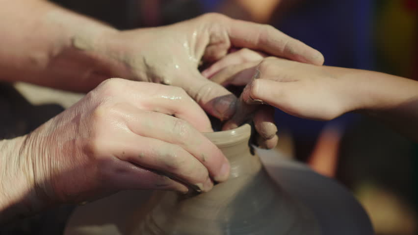 Potter teaches children to make pots at a street fair. Close-up, only the hands are visible