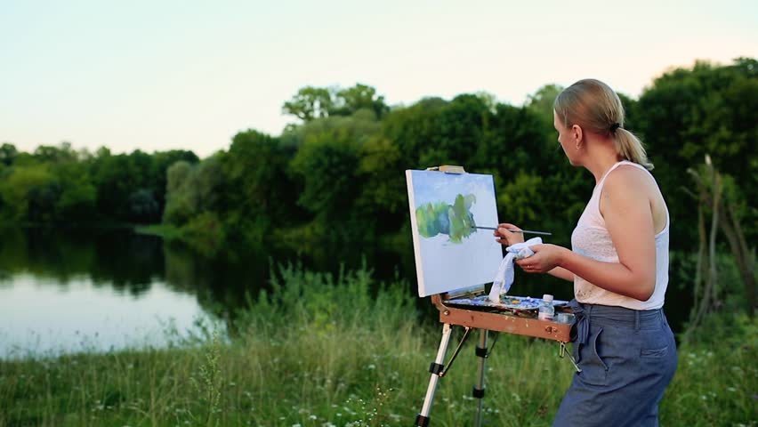 A woman artist with a brush and polytray in her hands draws on canvas against the backdrop of nature. The artist draws on the easel. Artist at work   Shutterstock HD Video #30599521