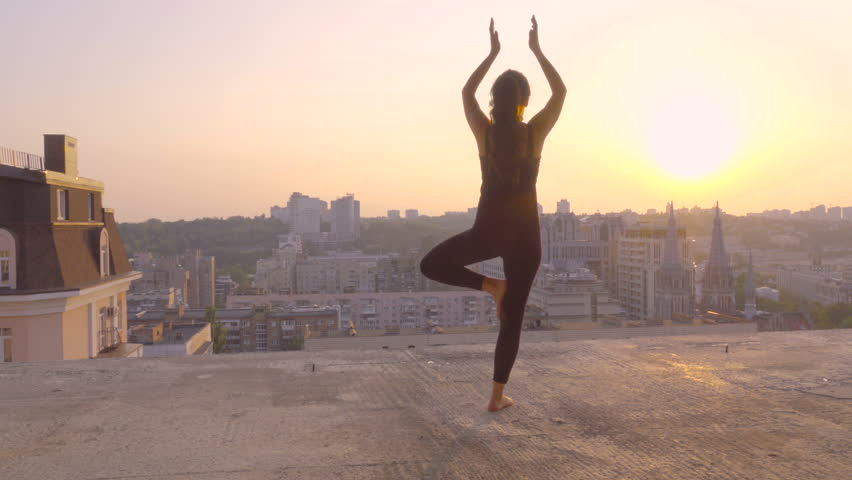 Sporty brunette doing yoga exercise on the rooftop at sunset