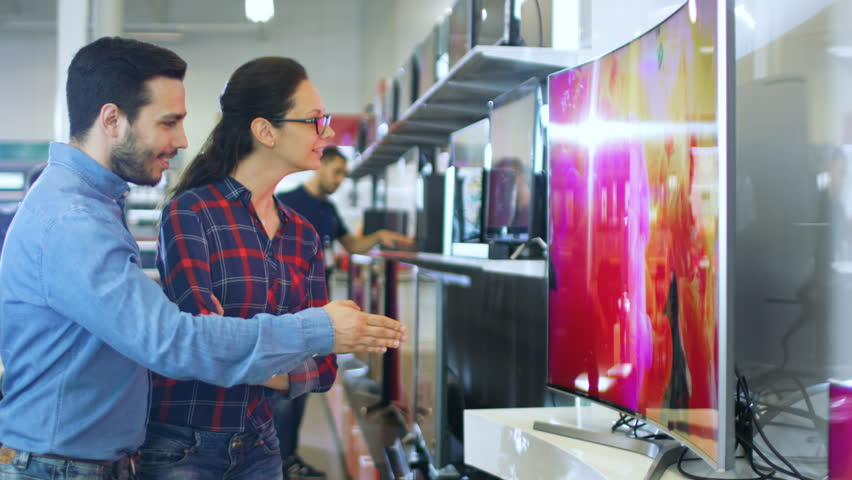 Young Couple Shopping for a New 4K UHD Television Set in the Electronics Store. They're Deciding on the Best Model for Their Happy Family House. Shot on RED EPIC-W 8K Helium Cinema Camera. | Shutterstock HD Video #30615001