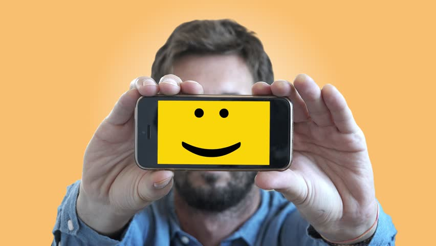 Happy Guy Smiley Face On Smartphone Screen. Man shows his feelings through a smartphone with a Smiley face on screen