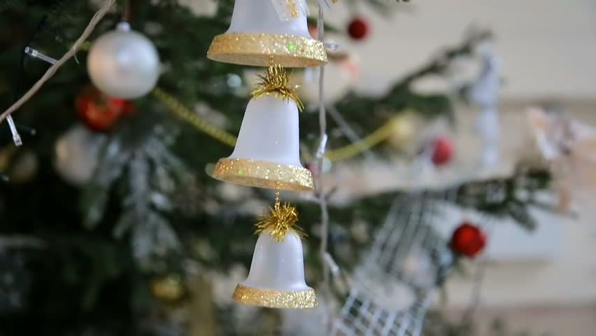 Golden toy bells hang on Christmas tree among of blinking colored garlands, close-up #30640183
