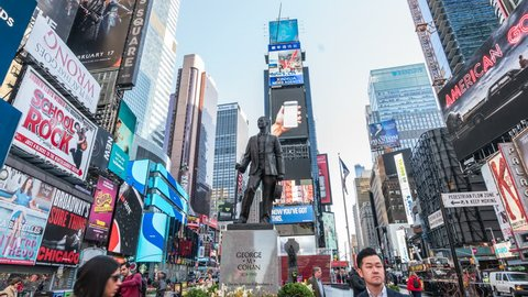 New York City, Circa 2017. George M. Cohan sculpture in Times Square. Hyperlapsed video, bright billboards with famous brand advertisement in the background. Manhattan, United States.