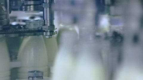 Milk production line. Production line at dairy factory. Automated production line at milk factory. Food industry. Milk pouring into plastic bottle at dairy plant