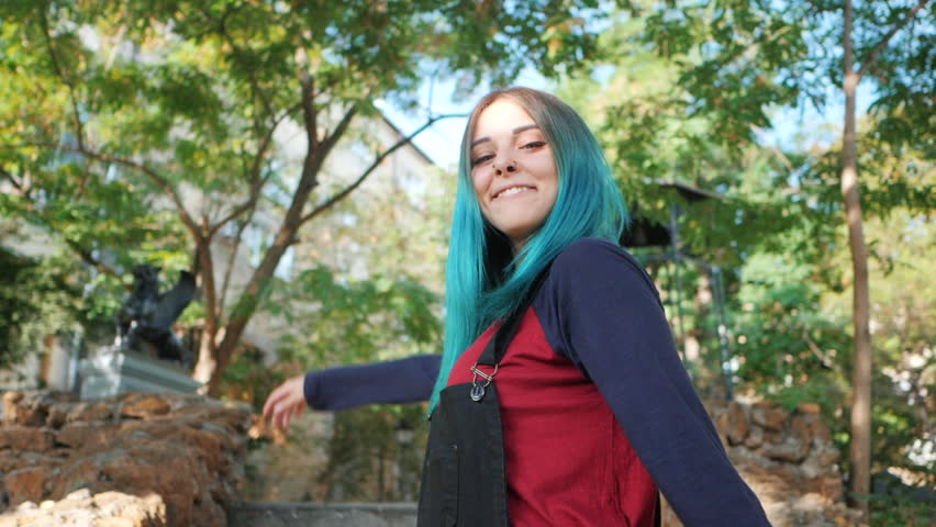 Street punk or hipster girl enjoying empty old European park. Portrait of teen girl with blue dyed hair,piercing in nose,violet lenses and unusual hairstyle dancing.Carefree concept. Slow motion.