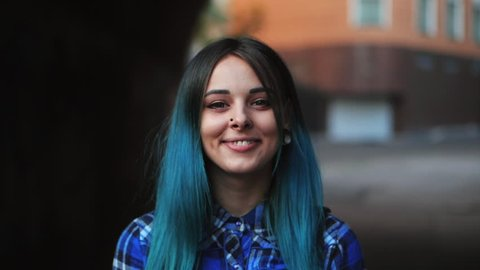 Street punk or hipster girl with blue dyed hair. Woman with piercing in nose, violet lenses, ears tunnels and unusual hairstyle stands in city. Slow motion.