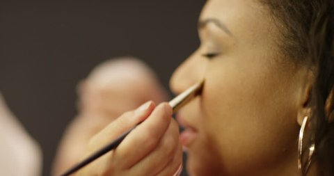 4K Close up on face of African American model having makeup applied by professional makeup artist. Slow motion.