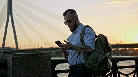 Well-dressed trendy man with nobile phone in a city