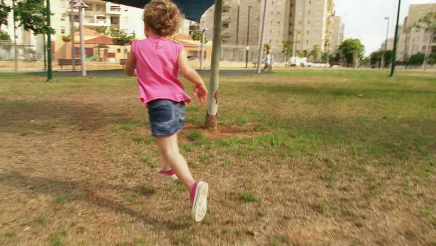Girl running at playground / park in slow motion. Sequence.