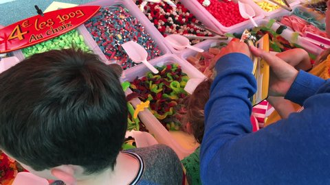 Children with mom buying candy sweets from pick and mix market stall