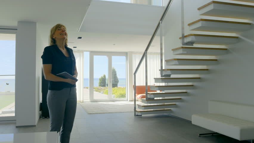 Professional Real Estate Agent Welcomes Beautiful Young Couple into Spacious and Modern Home. With Floor to Ceiling Windows and Seaside View. Shot on RED EPIC-W 8K Helium Cinema Camera. | Shutterstock HD Video #30700171
