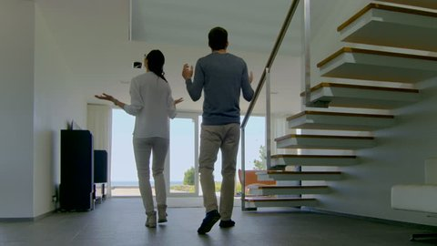 Beautiful Young Couple Enters Their Newly Purchased House, They're Very Happy. Their Luxury Home is Bright, Modern and Has Floor to Ceiling Windows and Seaside View.Shot on RED EPIC-W 8K Helium Camera